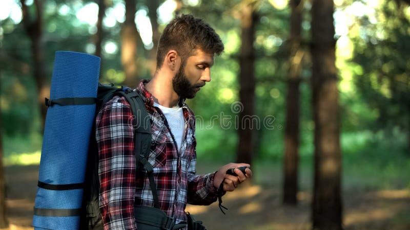 Mannen förlorade i skog genom att använda kompasset för att navigera och att finna utfarten från trän royaltyfria foton