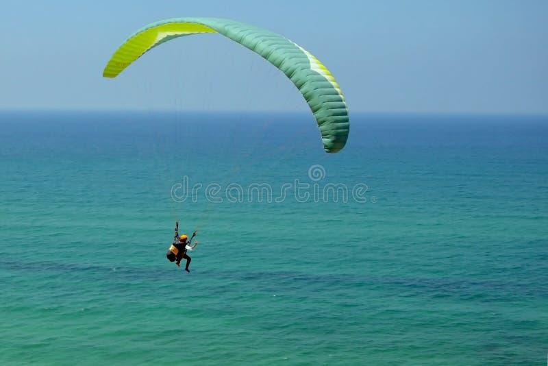 Mannen flyger på den gröna paraglideren i himlen ovanför det azura havet Jämvikt extrema sportar, livsstil Medelhav Israel royaltyfria bilder
