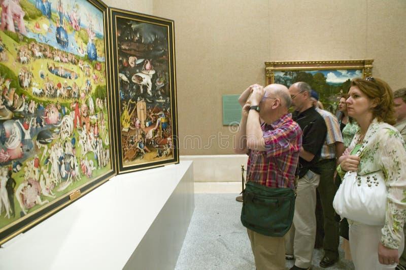 Mannen fotograferar trädgården av jordiska fröjder av Hieronymus Bosch, i museet de Prado, det Prado museet, Madrid, Spanien arkivfoto