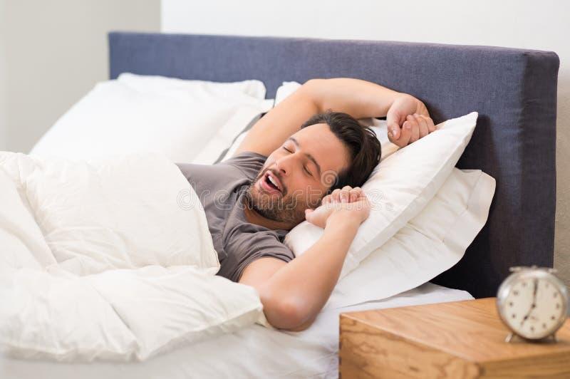 Mannen gäspar i säng royaltyfria bilder