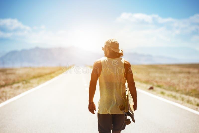 Mannen går för brädevägen för skateboarden den långa huvudvägen arkivbild
