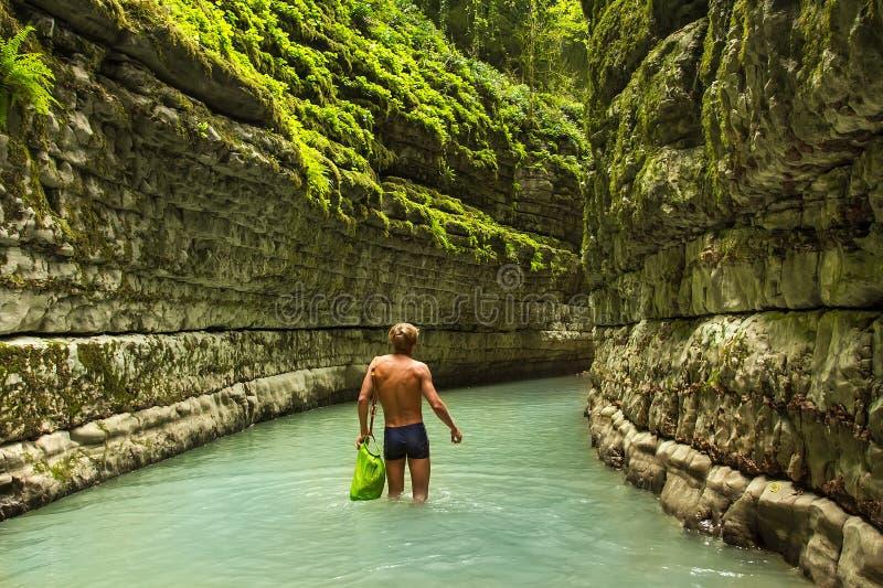 Mannen går på den djupa kanjonen i djungeln arkivfoton