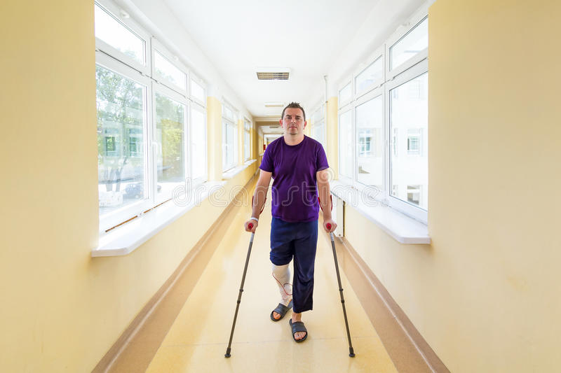 Mannen går på kryckor arkivfoto
