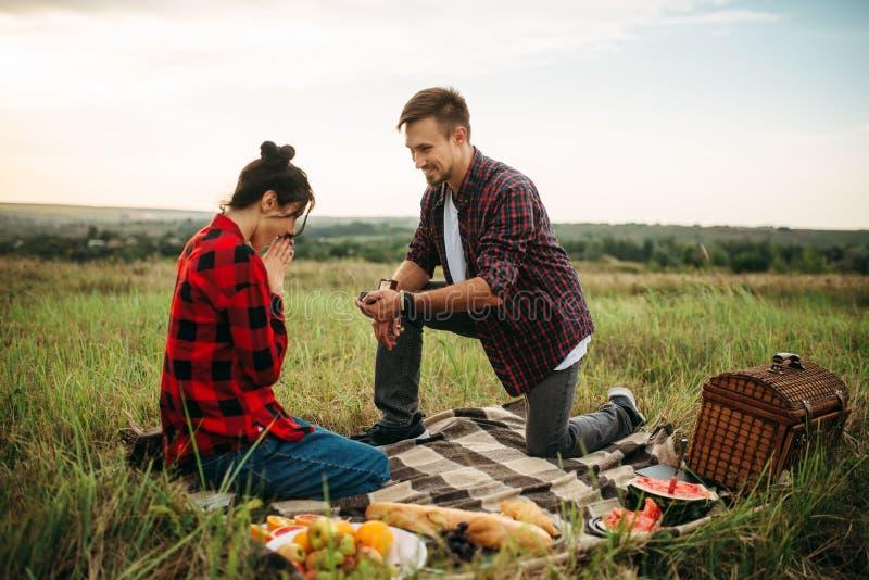 Mannen gör ett förbindelseförslag på romantisk picknick royaltyfri bild