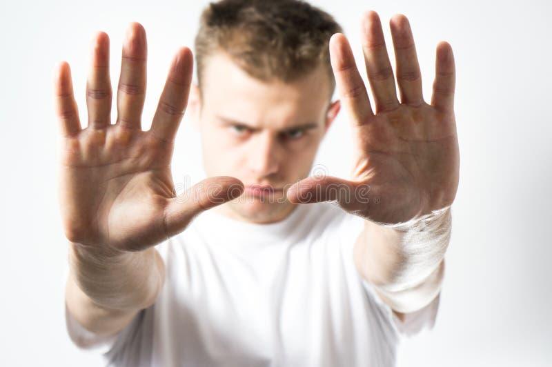 Mannen gör ett stopptecken med hans händer, en missnöjd framsida arkivfoton