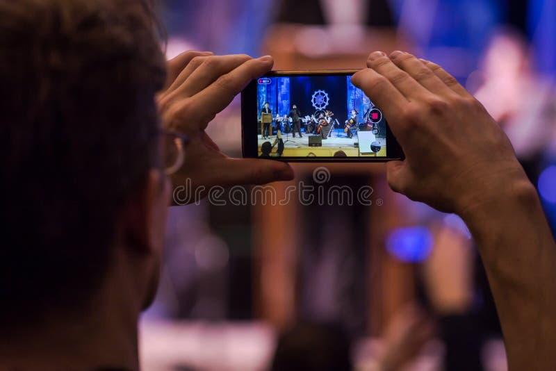Mannen gör fotoet och videoen på smartphonen på konsertcloseupen royaltyfri foto