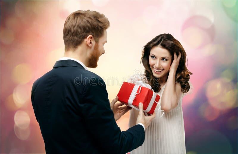 Mannen gör gåva till hans härliga flickvän royaltyfri bild