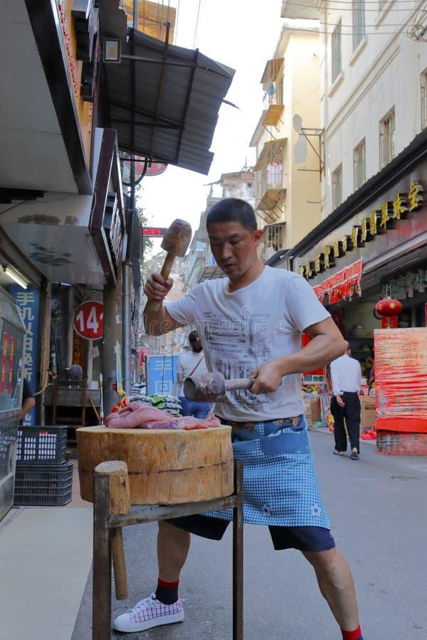 Mannen gör köttstoppning vid trähammaren, inte kniv royaltyfri fotografi
