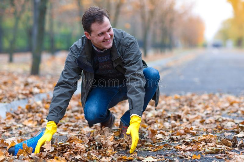 Mannen gör ren de stupade sidorna i hösten parkerar fotografering för bildbyråer