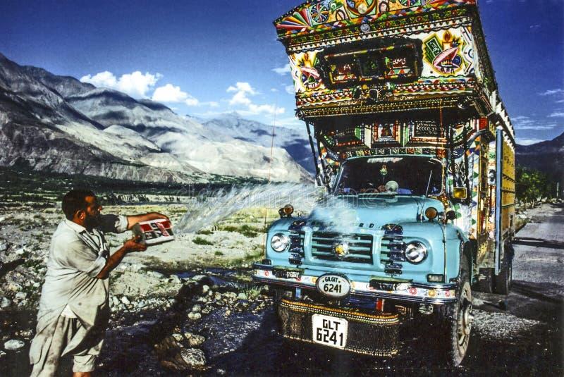 Mannen gör ren hans overland lastbil med vatten från en liten vik fotografering för bildbyråer