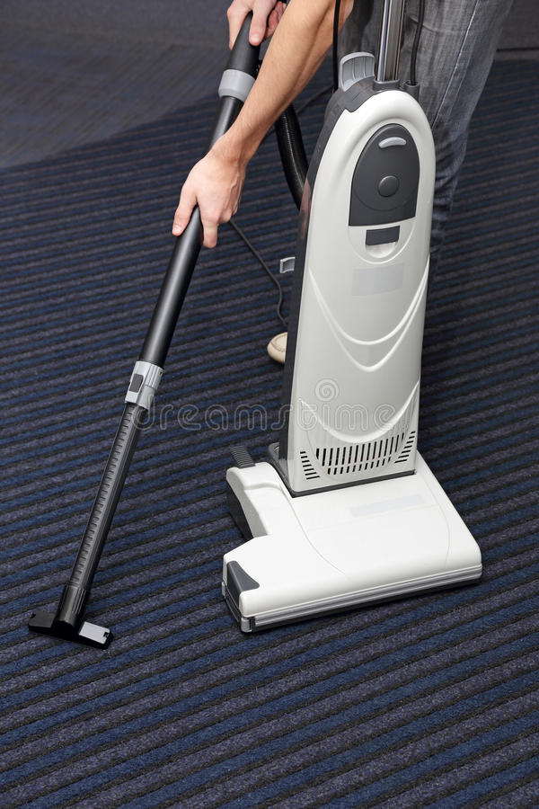 Mannen gör ren mattan arkivbild