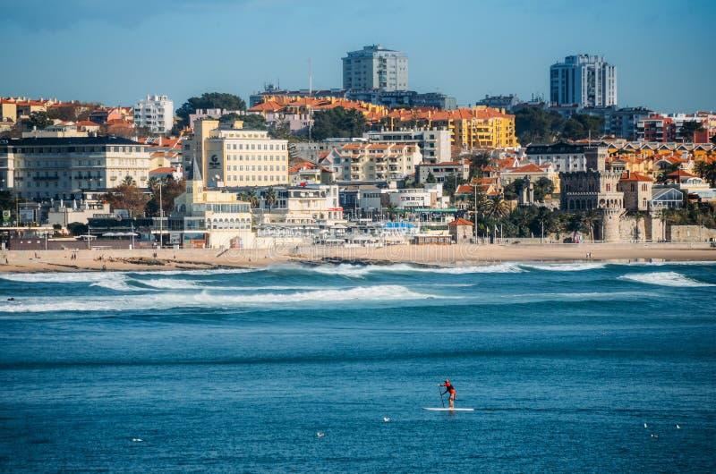 Mannen gör står upp skoveln som förbiser kusten av Estoril nära Lissabon, Portugal arkivfoton