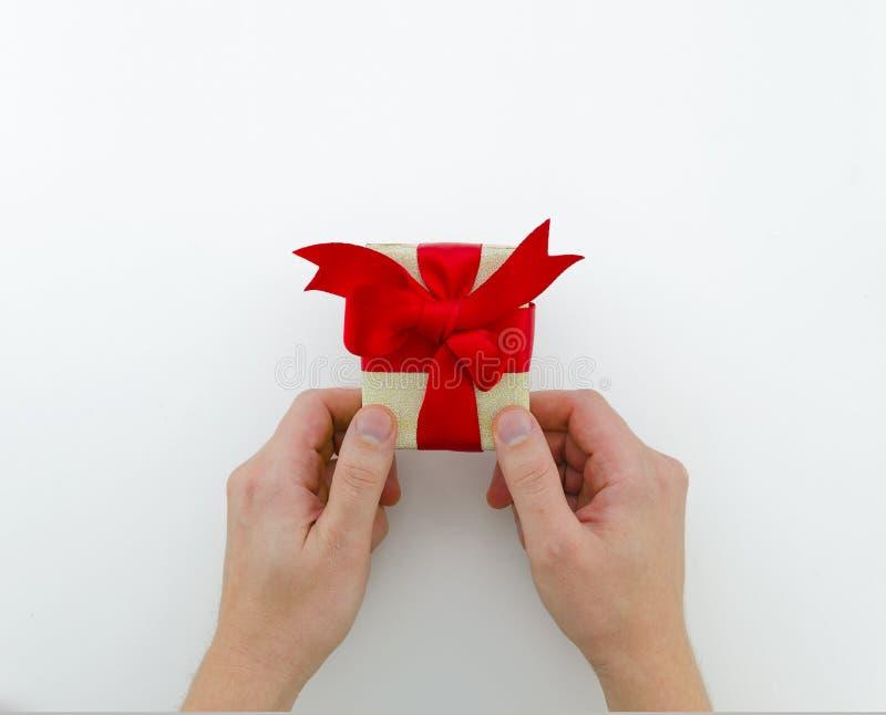 Mannen ger en elegant glansig gåva Manhols i hans lilla gåvaask för händer med det röda bandet Bästa sikt, lekmanna- lägenhet kop royaltyfri bild