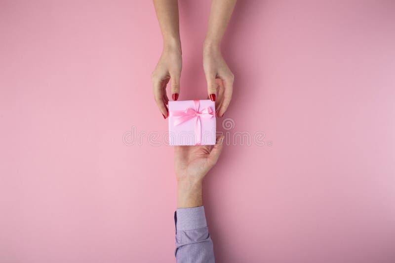 Mannen ger en flicka en gåva från handen för att räcka, asken som slås in i dekorativt papper på en rosa pastellfärgad bakgrund,  arkivfoto