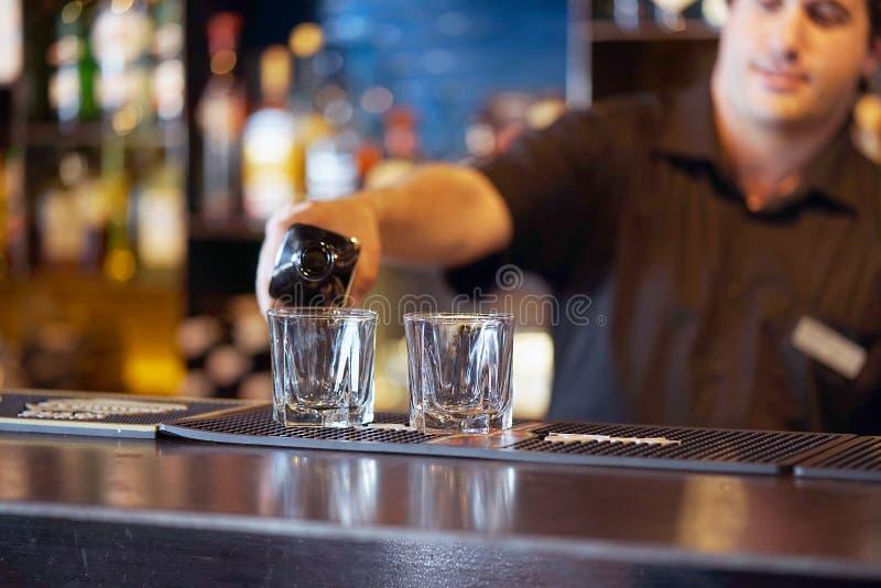 Mannen ger ett exponeringsglas av whisky royaltyfria foton