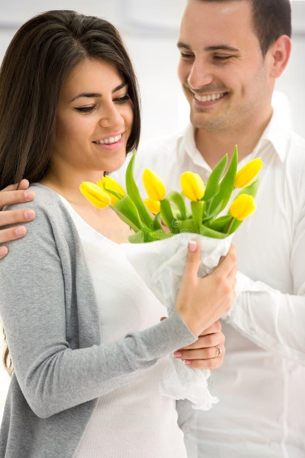 Mannen ger hans flickvän blommor royaltyfria foton