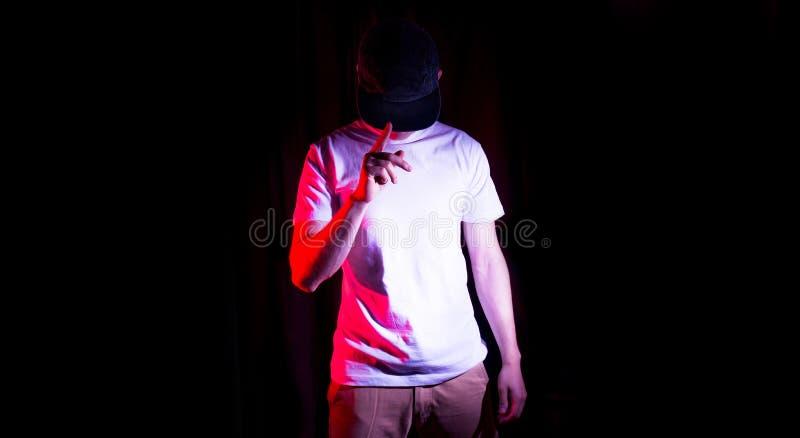 Mannen, grabb i den tomma svarta baseballmössan, på en svart bakgrund, åtlöje upp, fritt utrymme, logopresentation, mall för tryc royaltyfri fotografi