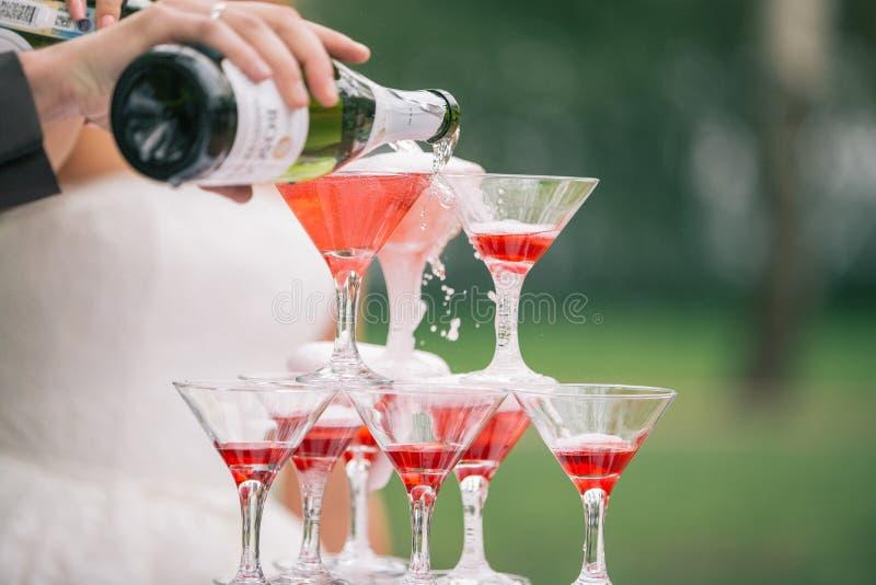 Mannen häller champagne på en pyramid av exponeringsglas royaltyfria bilder
