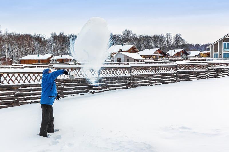 Mannen häller ut det kokande vattnet av en slev på gatan, en frost negativ 25 grader royaltyfria foton