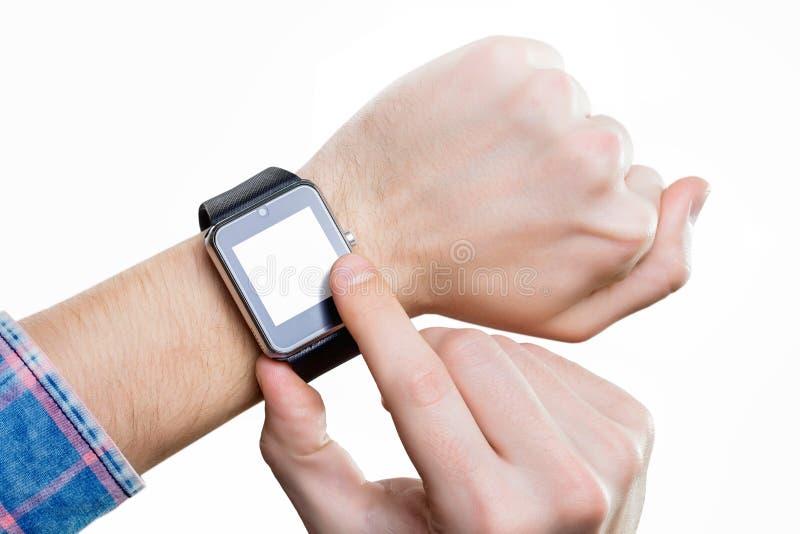 Mannen håller ögonen på på den smarta klockan med den tomma skärmen förestående royaltyfri fotografi