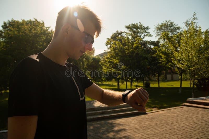 Mannen håller ögonen på på hans smarta klocka på solnedgången royaltyfri foto