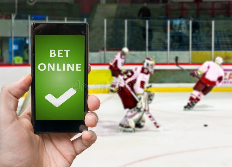 Mannen håller ögonen på ishockey och slå vad direktanslutet via smartphonen arkivfoto