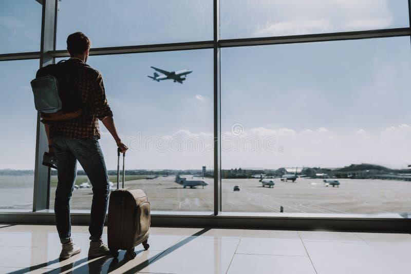 Mannen håller ögonen på plant flyg från flygplats arkivfoton