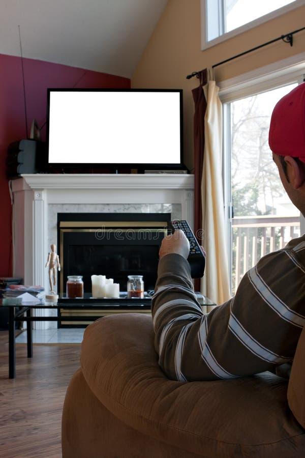 Mannen håller ögonen på TV:N royaltyfri foto