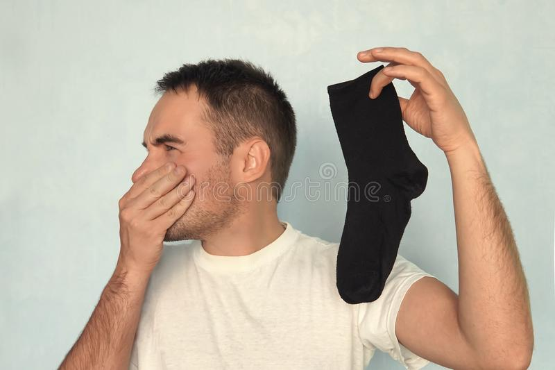 Mannen håller sockor, dålig lukt från slitna sockor stank stank, lukt, stank royaltyfria foton
