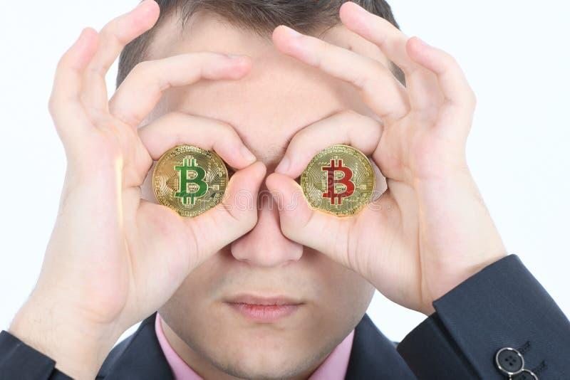 Mannen h?ller bitcoinen f?r cryptocurrency tv? f?r ?gat i st?llet den guld- i h?nder royaltyfria foton