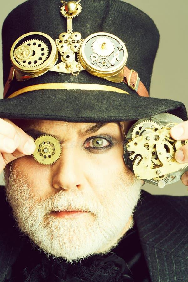 Mannen h?ller kugghjulet och kugghjul royaltyfri bild