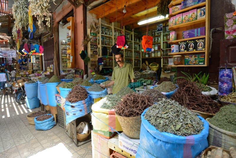 Mannen handlar kryddor i en marknad royaltyfria bilder
