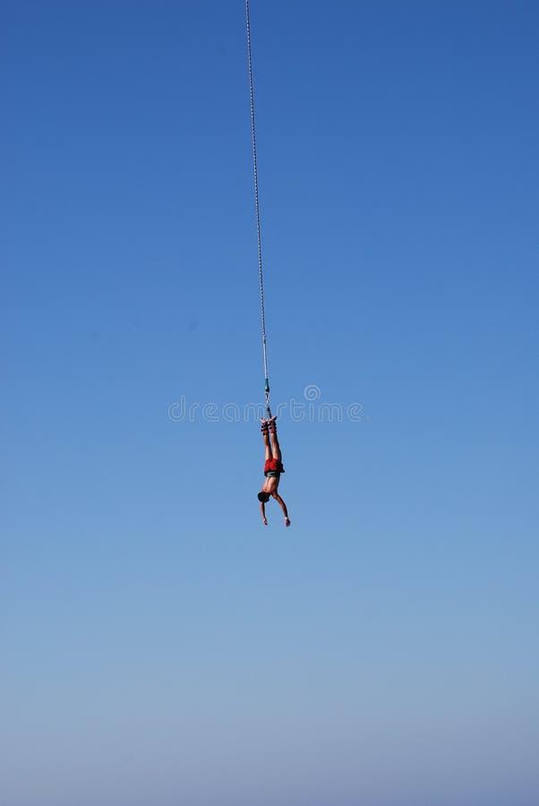 Mannen hoppar från en stor höjd som ropejumping arkivfoto