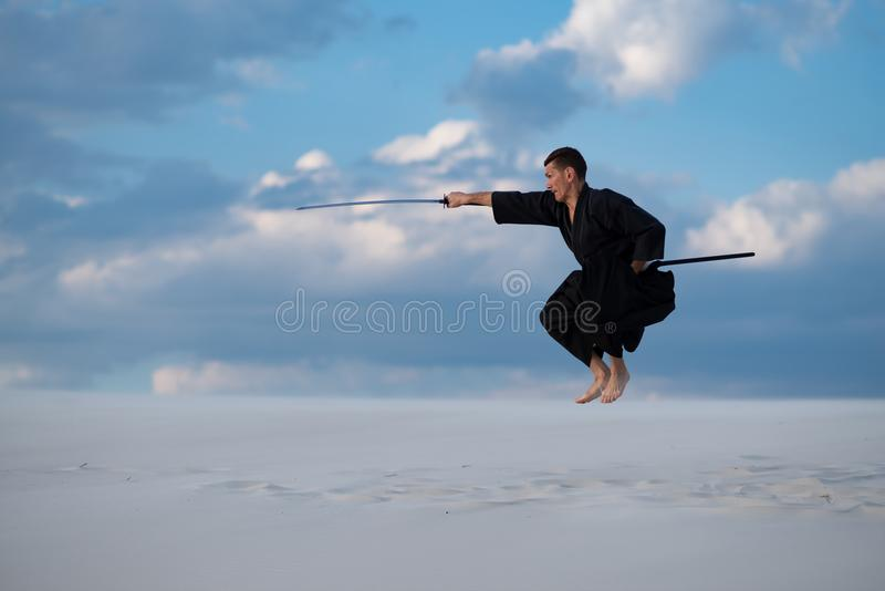 Mannen hoppar under utbildningskampsporter i öken royaltyfria foton