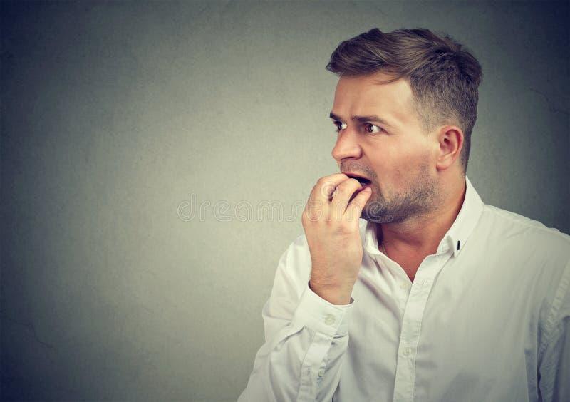 Mannen, i att bita för nöd, spikar royaltyfria foton