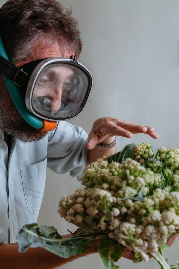 Mannen, i att simma maskeringen, rymmer blomk?len royaltyfria bilder