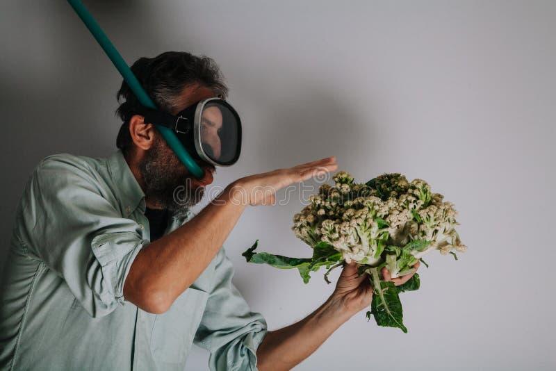 Mannen, i att simma maskeringen, rymmer blomk?len fotografering för bildbyråer