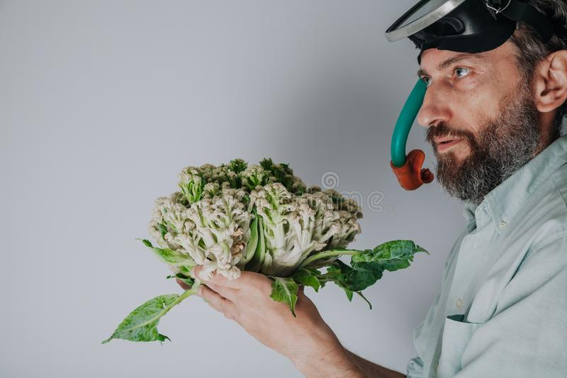 Mannen, i att simma maskeringen, rymmer blomk?len arkivbild