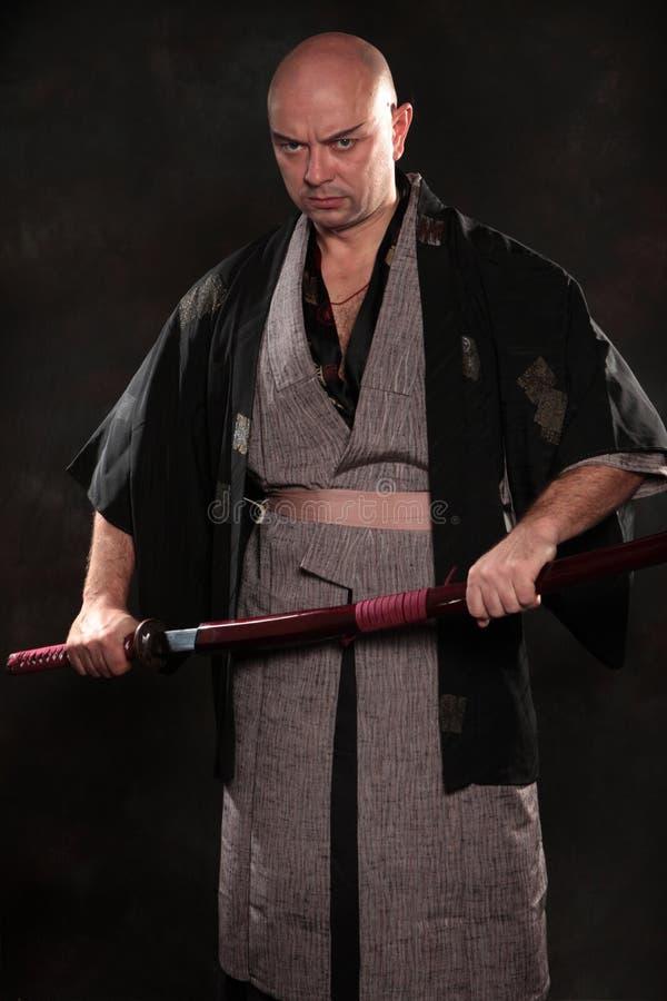 Mannen i bilden av en samuraj med svärdet i hand arkivbild