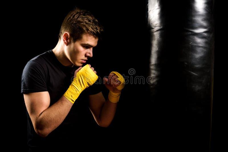 Mannen i boxningsjalar är utbilda och slå den tunga påsen royaltyfria bilder