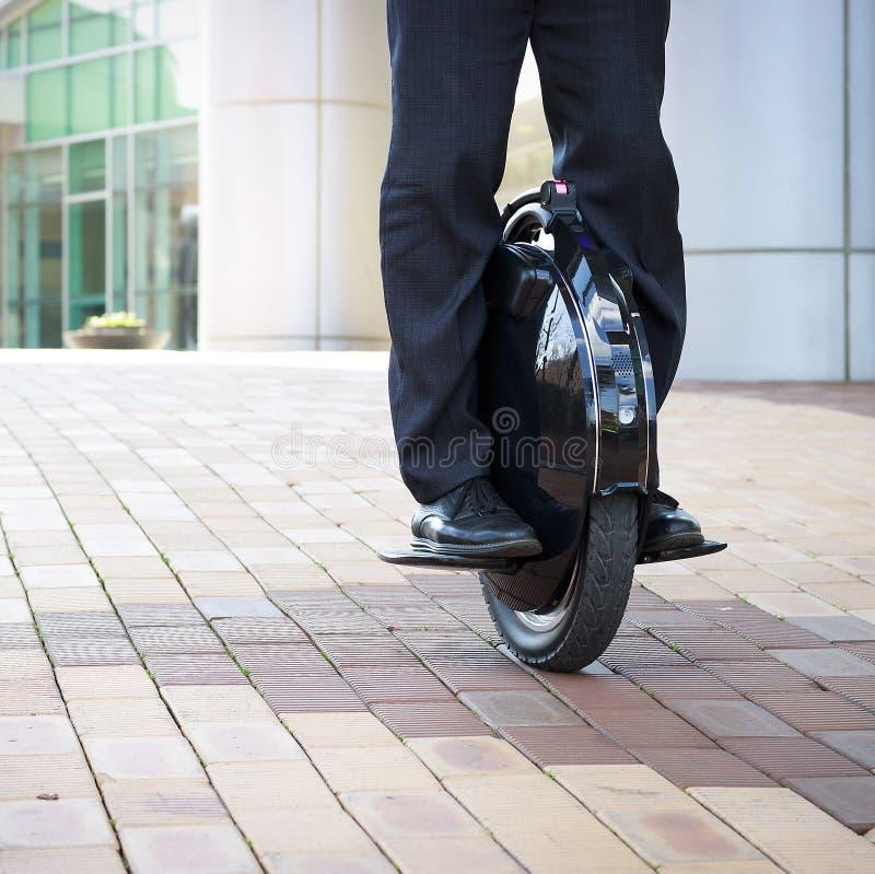 Mannen i byxa och skor kör på en elektrisk enhjuling, främre sikt arkivbilder