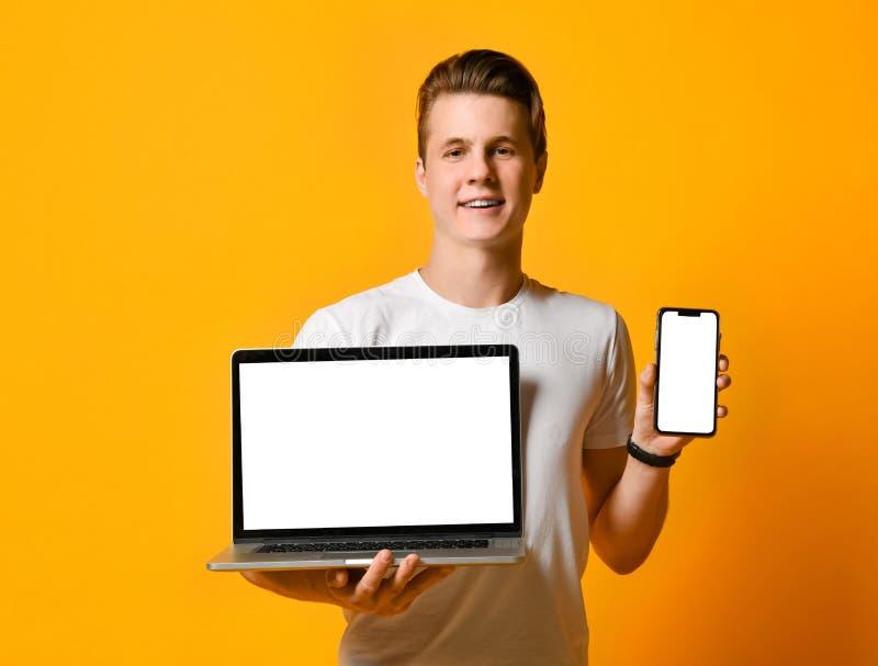 Mannen i den vita skjortan och att rymma en bärbar datordator och en mobil smart telefon, anseendet visar skärmen av telefonen oc arkivfoto