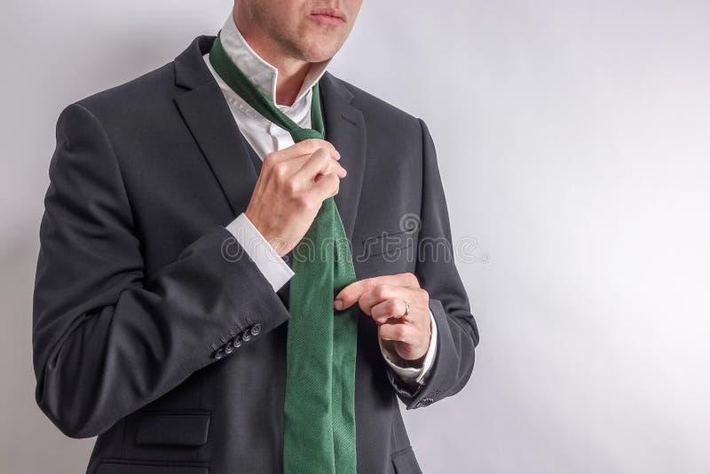 Mannen i den vita skjortan och den svarta dräkten får klädda/klädde av royaltyfria bilder