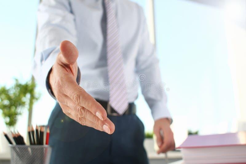Mannen i dr?kt och bandet ger handen som h?lsningar arkivfoton