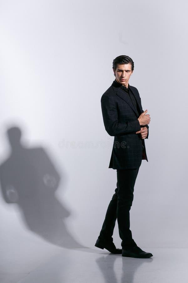 Mannen i elegant dräkt, poserar med attitudinen, isoalted på en vit bakgrund Trycka på hans knapp på omslaget royaltyfria foton