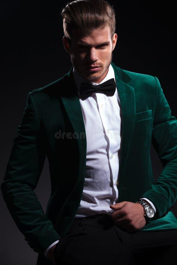 Mannen i elegant grön sammetdräkt sitter på en stol arkivfoton