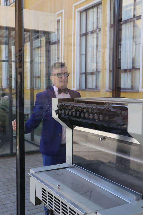 Mannen i en blå dräkt ser tryckpressen bak exponeringsglaset royaltyfri bild