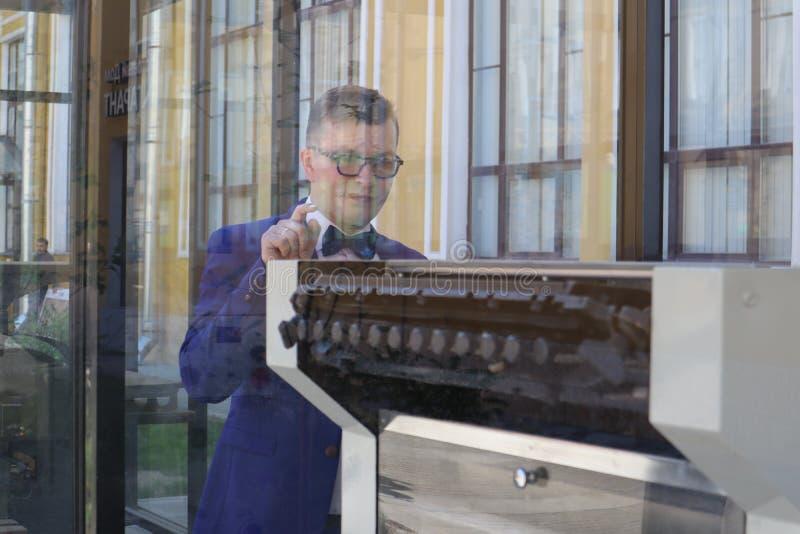 Mannen i en blå dräkt ser tryckpressen bak exponeringsglaset royaltyfria bilder