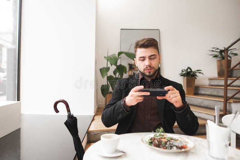 Mannen i en dräkt sitter i en hemtrevlig ljus restaurang och väljer upp mat på en smartphone arkivbild