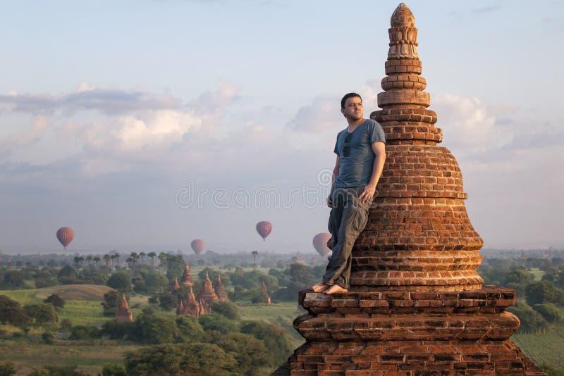 Mannen i en romantiker poserar anseende på taket mot bakgrunden av staden av Bagan och ballonger royaltyfri bild